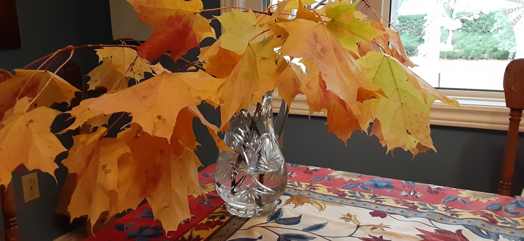 Crystal vase filled with maple leaf branches